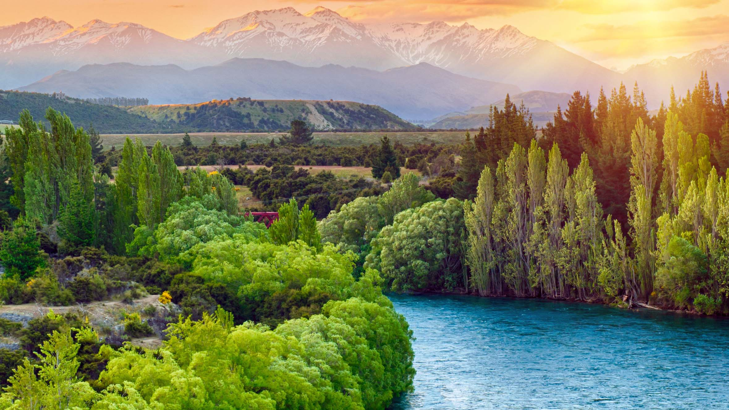A river flows through a lush valley with mountains and a sunset behind