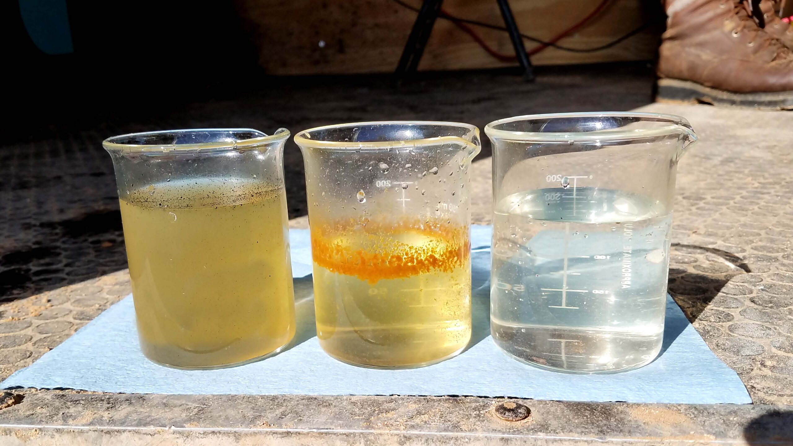 Three jars, raw to treated, left to right, sit in a PeroxyMAX trailer at a reuse site.