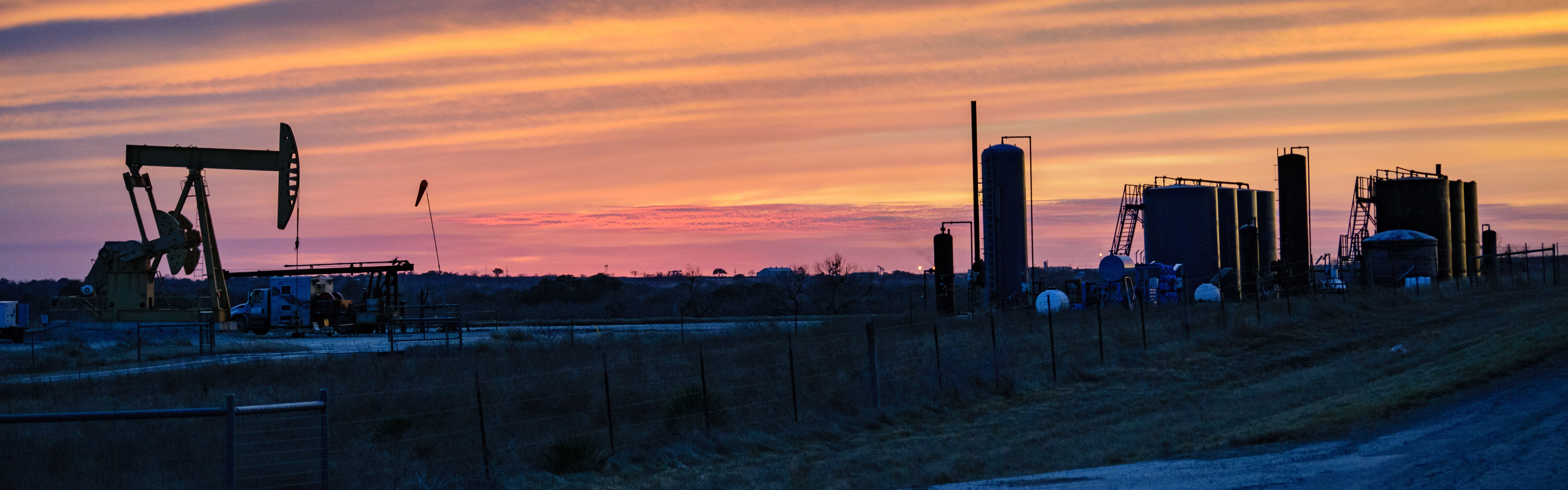 Oil and gas pump in field at sunset