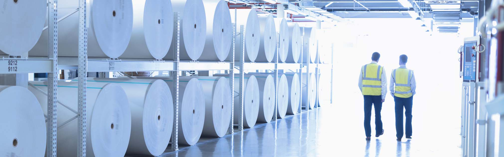 Pulp and paper mill workers walk down a hall next to reams of paper.