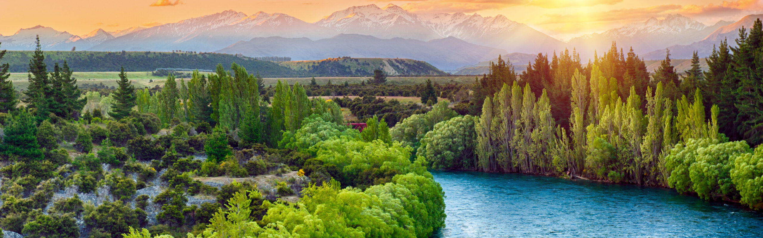 A clean river flows through a lush valley, with mountains in the background