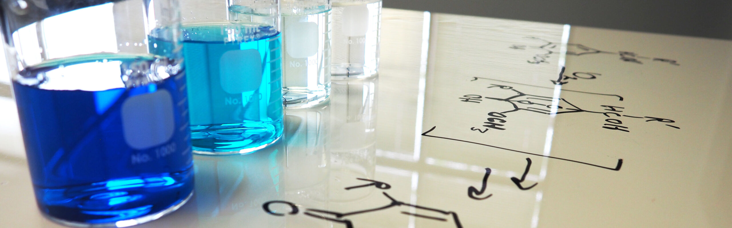 Jars from blue to clear represent PeroxyMAX oxidant technology. A chemical equation is seen in the foreground