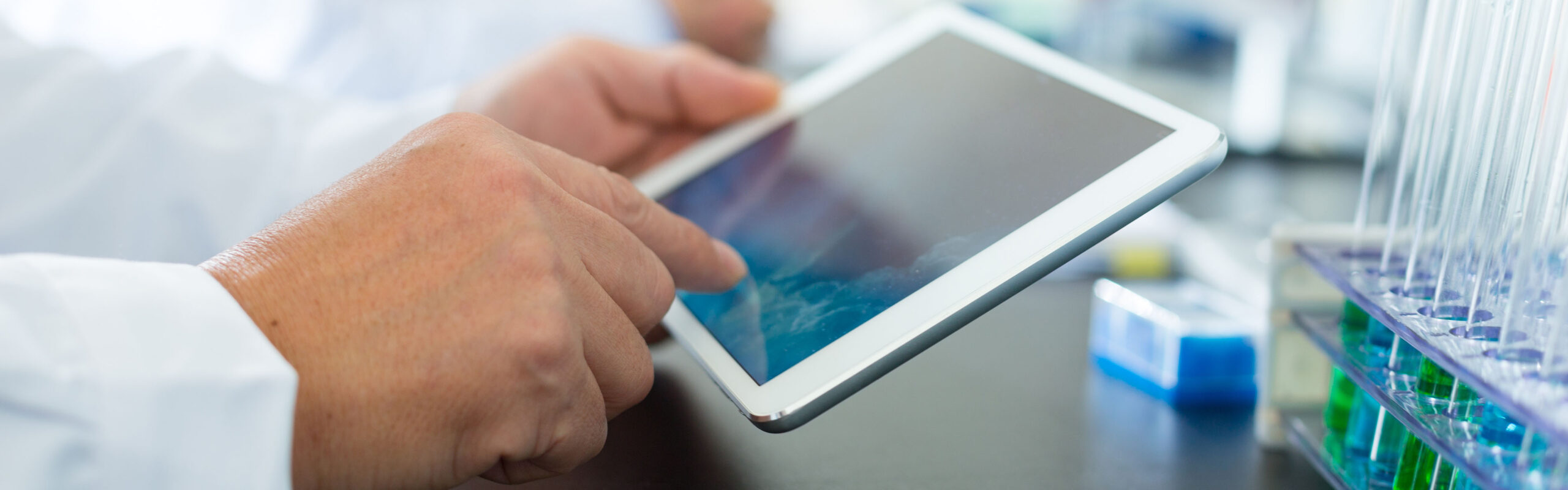 A chemist works on a tablet in the lab